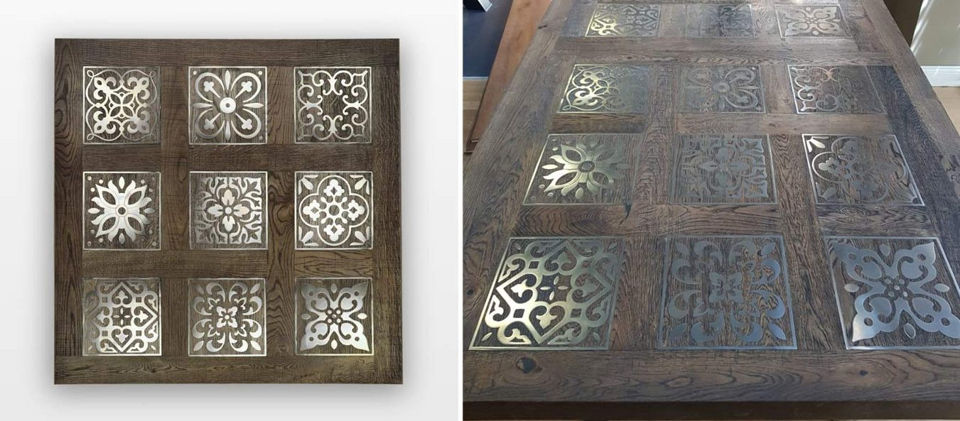 A section of wood flooring with 9 decorative metal inlays designed into the top of a table.