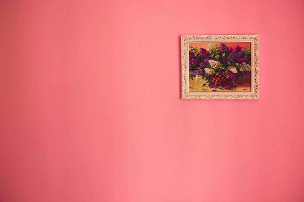 An interior wall painted a vibrant beautiful pink with a hanging framed floral painting on the right side.