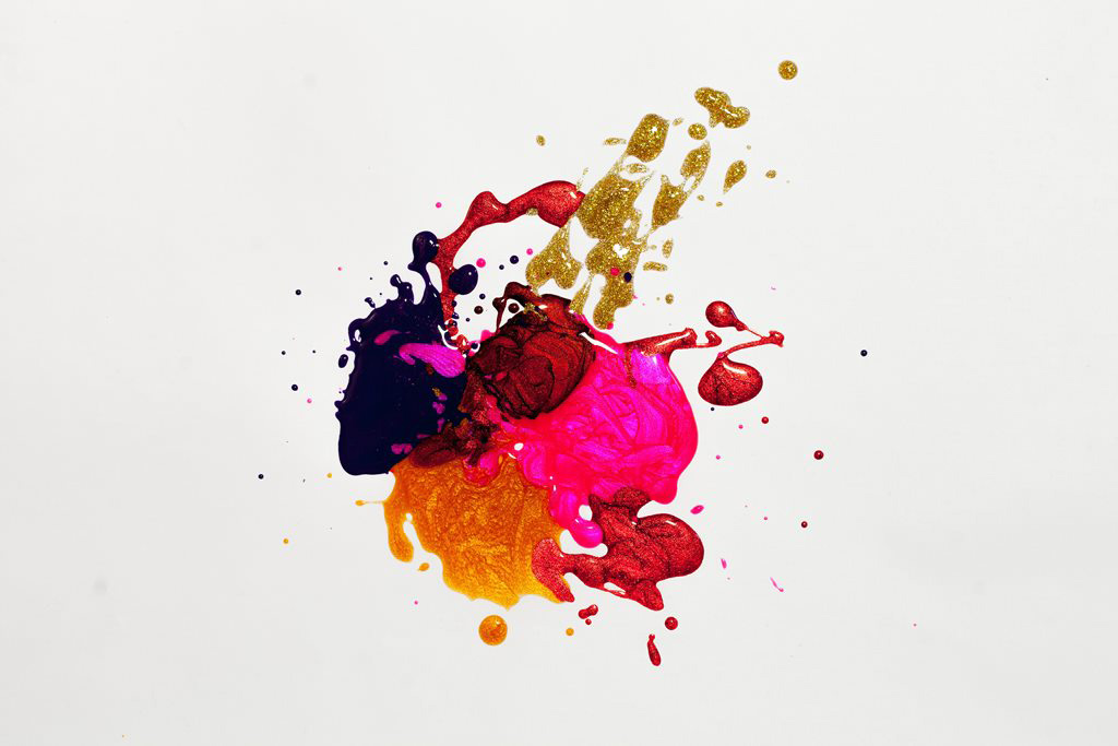 A multi coloured splatter of iridescent paint on a white background.
