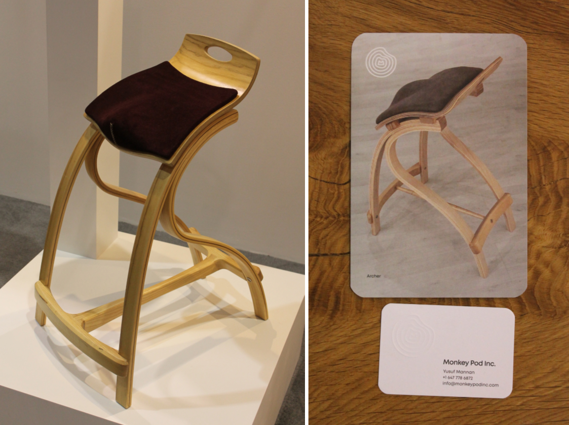 A standing chair made of light coloured wood, with a dark brown seat cushion.