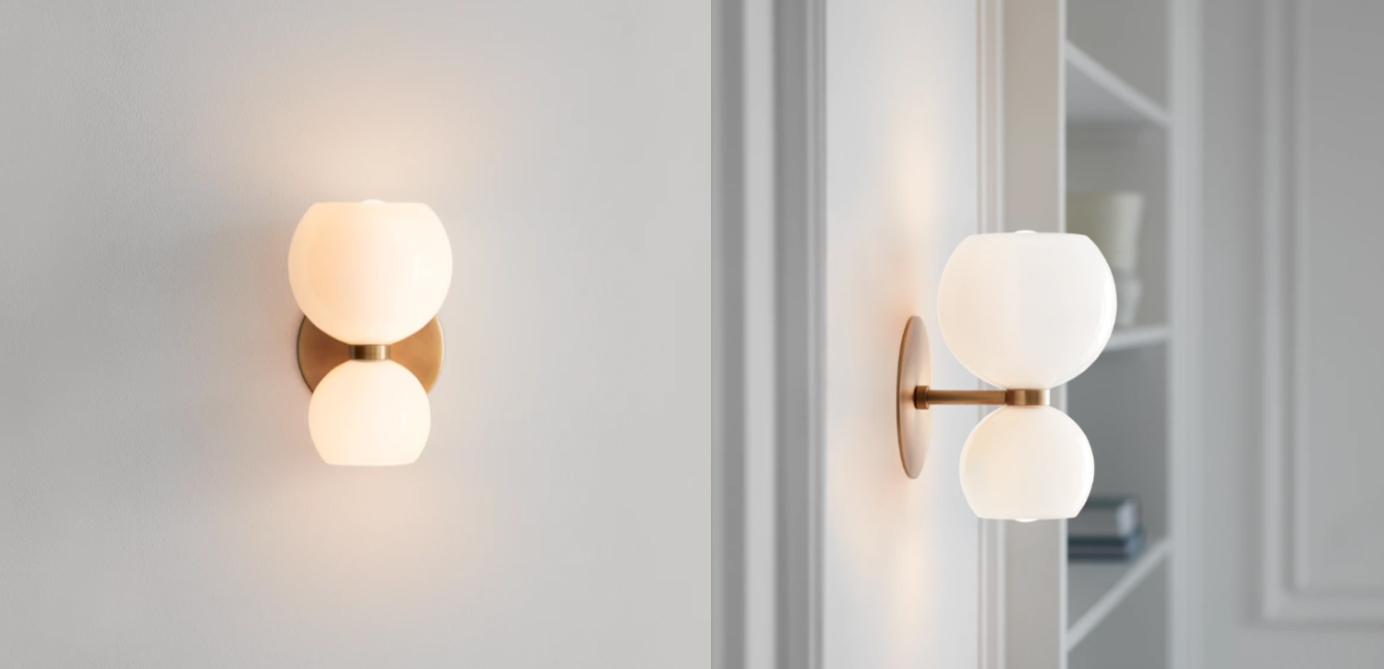 A modern wall sconce with a brass backplate and two spheres of white glass stacked on top of each other.