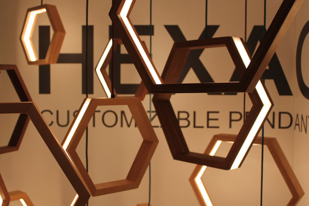 Multiple hexagon shaped lights made from LED and wood hanging in a display.