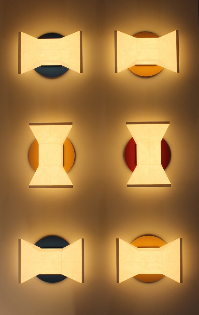 Six wall sconces with paper shades and coloured back plates mounted together in a rectangular shape.