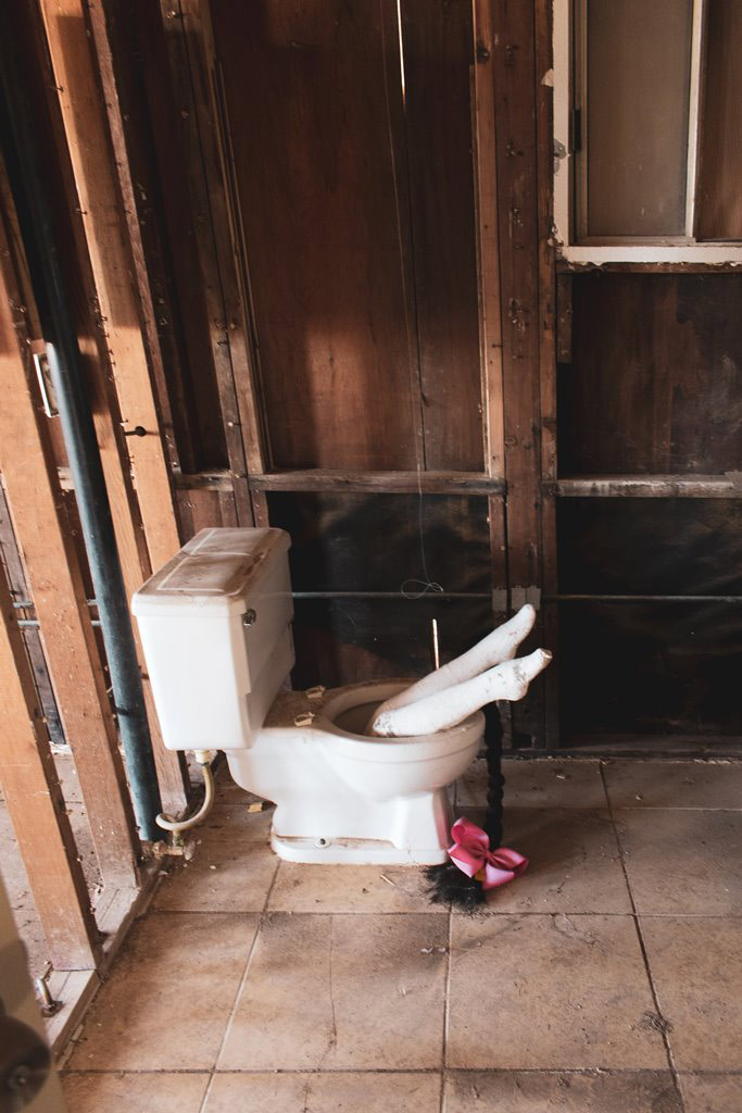 :   In an old bathroom that has been demo'd to the studs there is a dirty white toilet with a pair of legs in white stockings poking out of the toilet as if the occupant fell in and was partially flushed down.