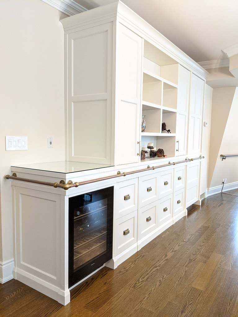Transitional style white custom-built cabinetry with bar fridge, built in freezer, open bookshelf, closed storage and decorative railing.