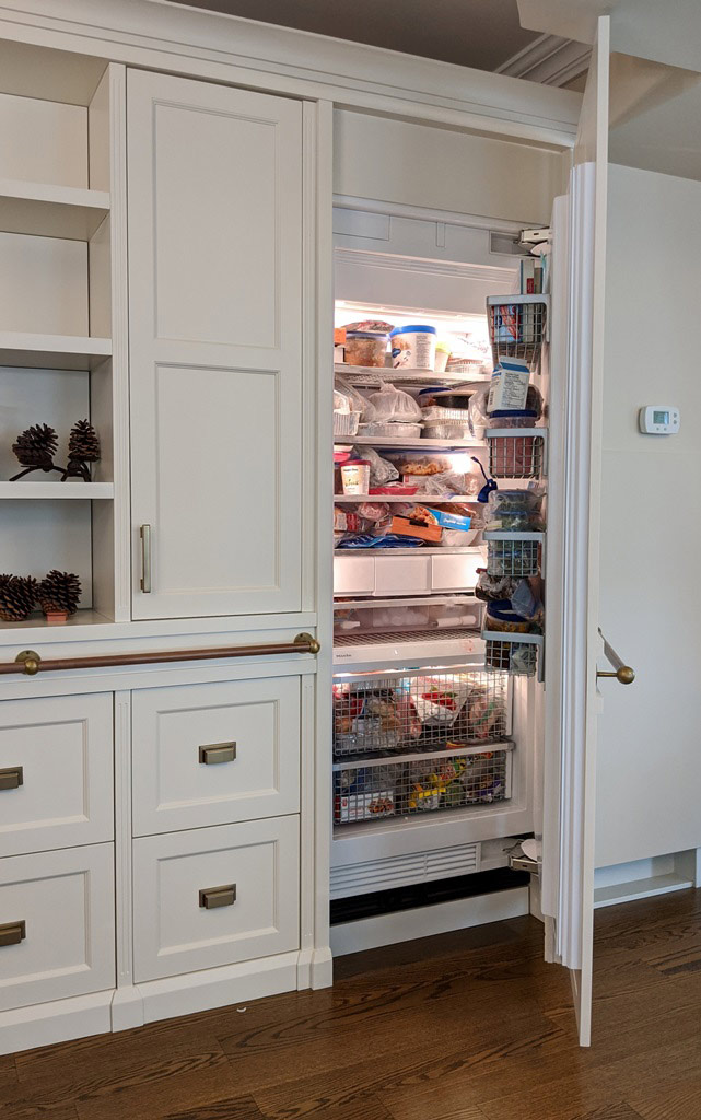 Transitional style white custom-built cabinetry, showing a view with the built-in freezer door open.