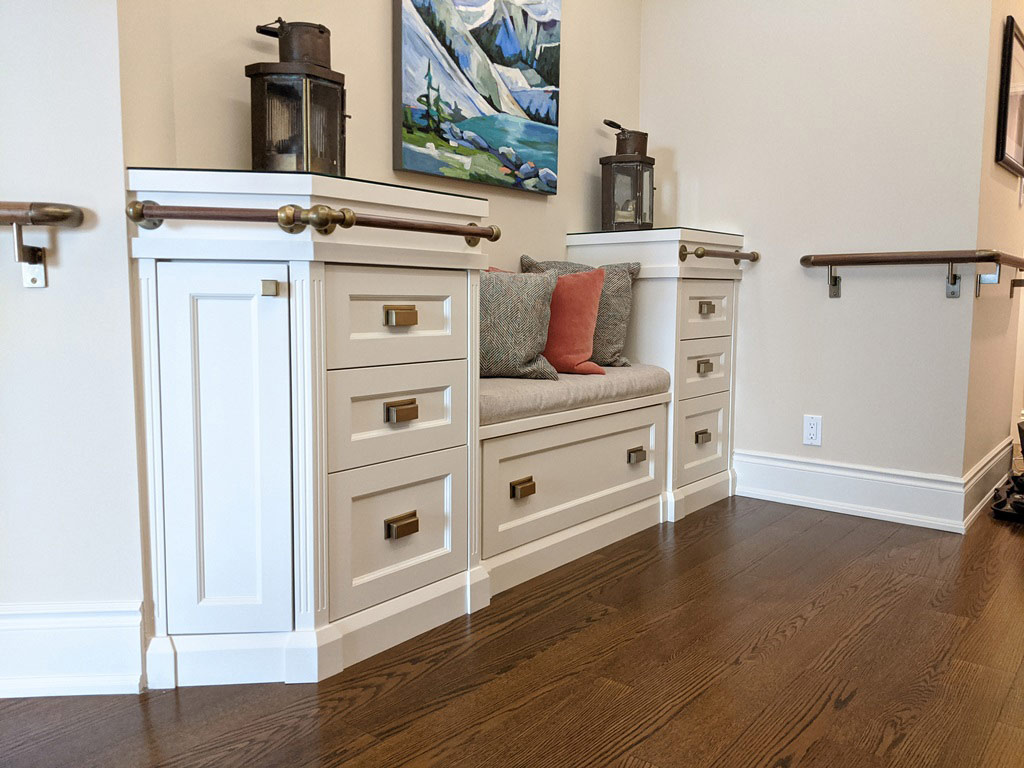 Transitional style white custom front entry cabinet with built in bench seating, decorative railing, and drawer storage.