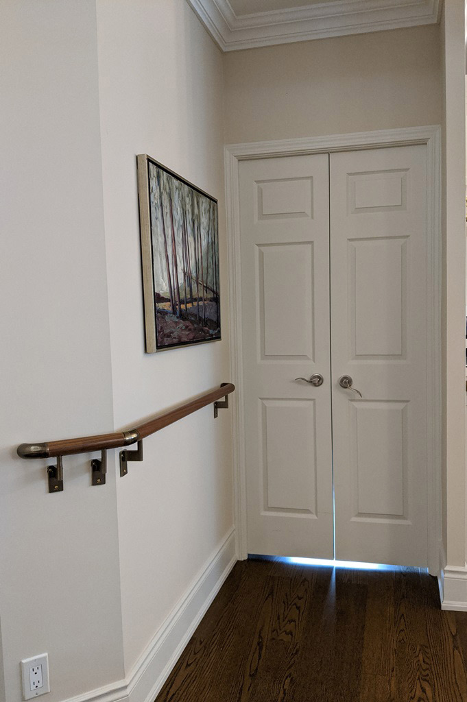 A section of hallway with a custom grab bar installation mounted to the wall and a double door entry into the adjacent office.