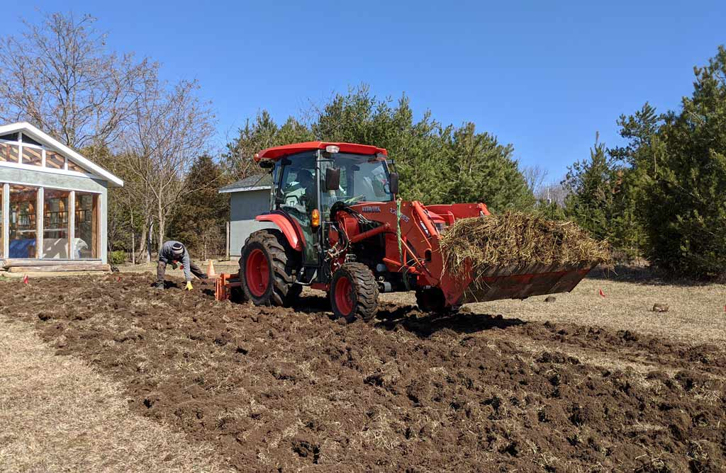 A large red tractor tilling a new garden bed and Justin collecting rocks from the soil.