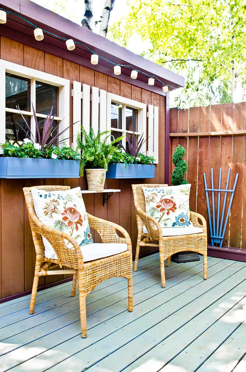 A backyard patio with two rattan chairs, flanked by an outdoor shed with bright blue window boxes.