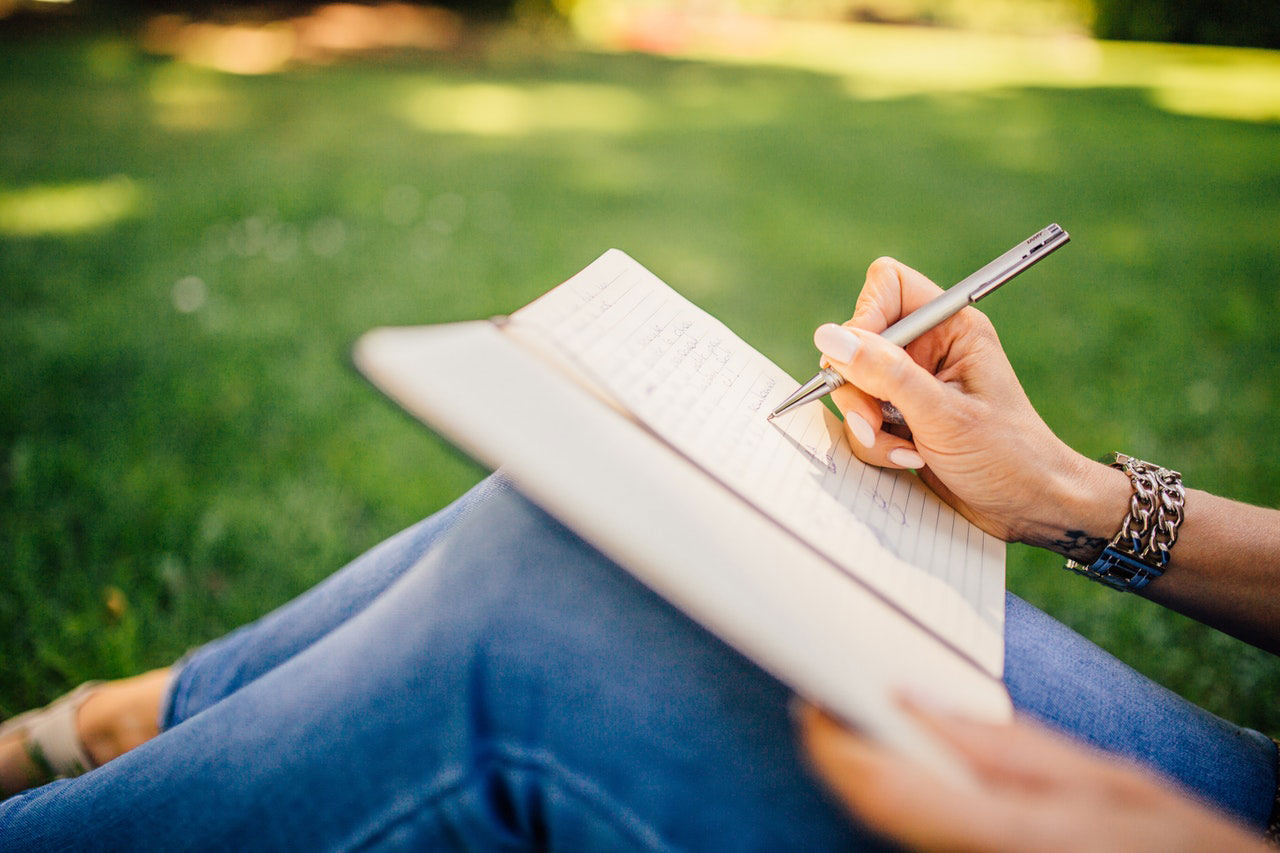 A woman sitting on the grass, writing in a journal which is on her knees.