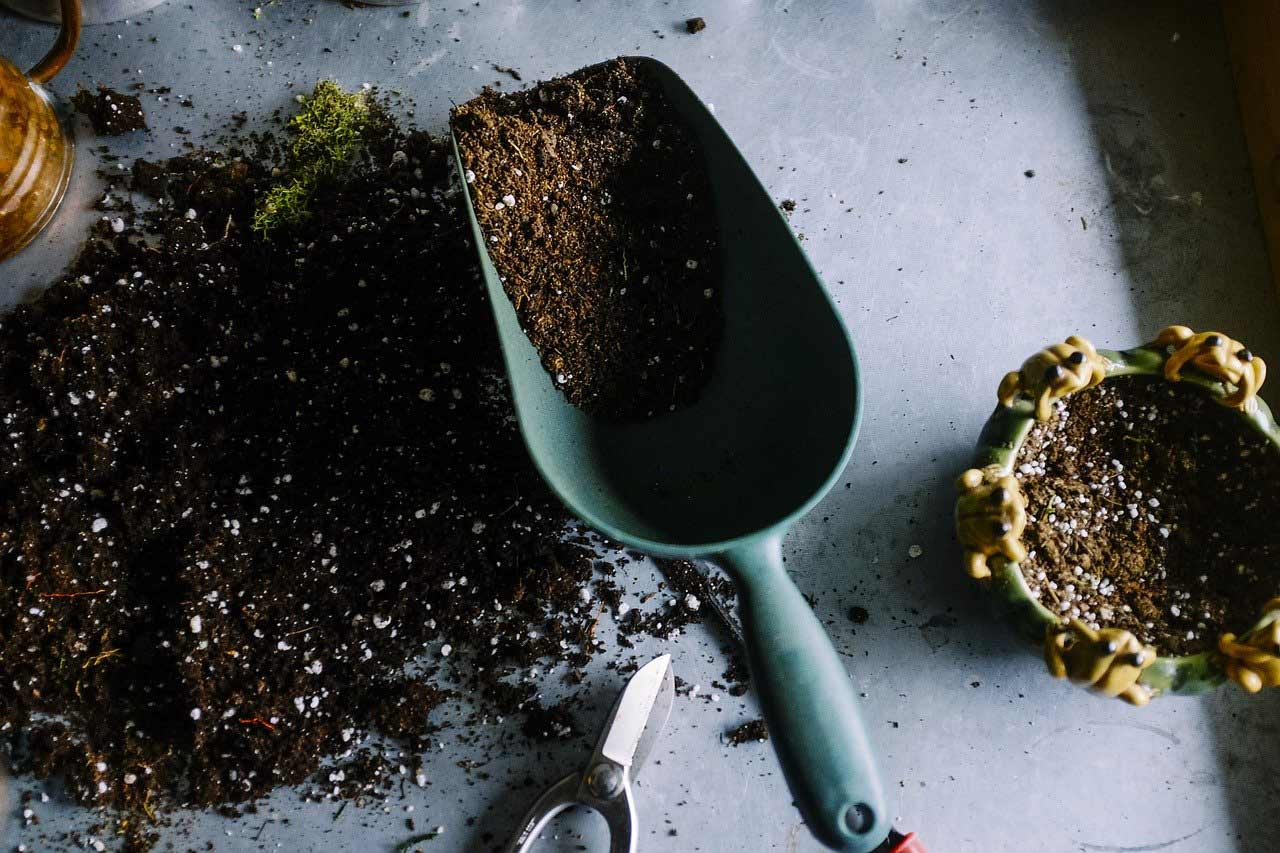 A large scoop partially filled with soil sits on top of a table with more soil.