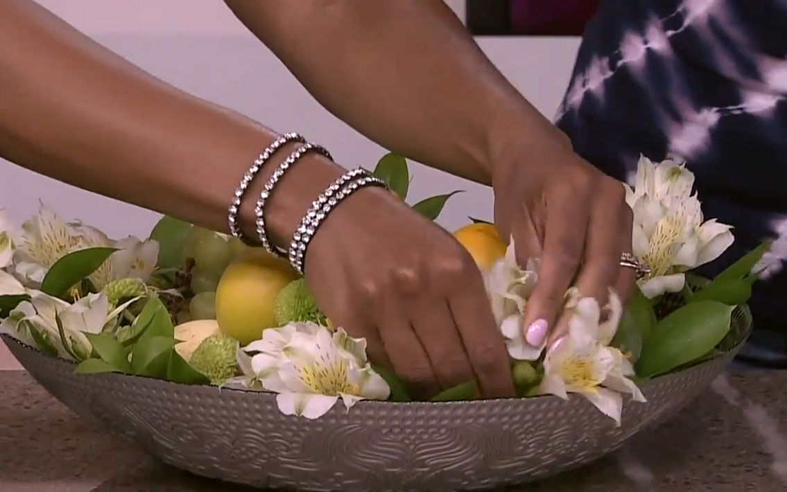 A close up of Tracy Moore's hands adding florals to a bowl of fruit and greenery.