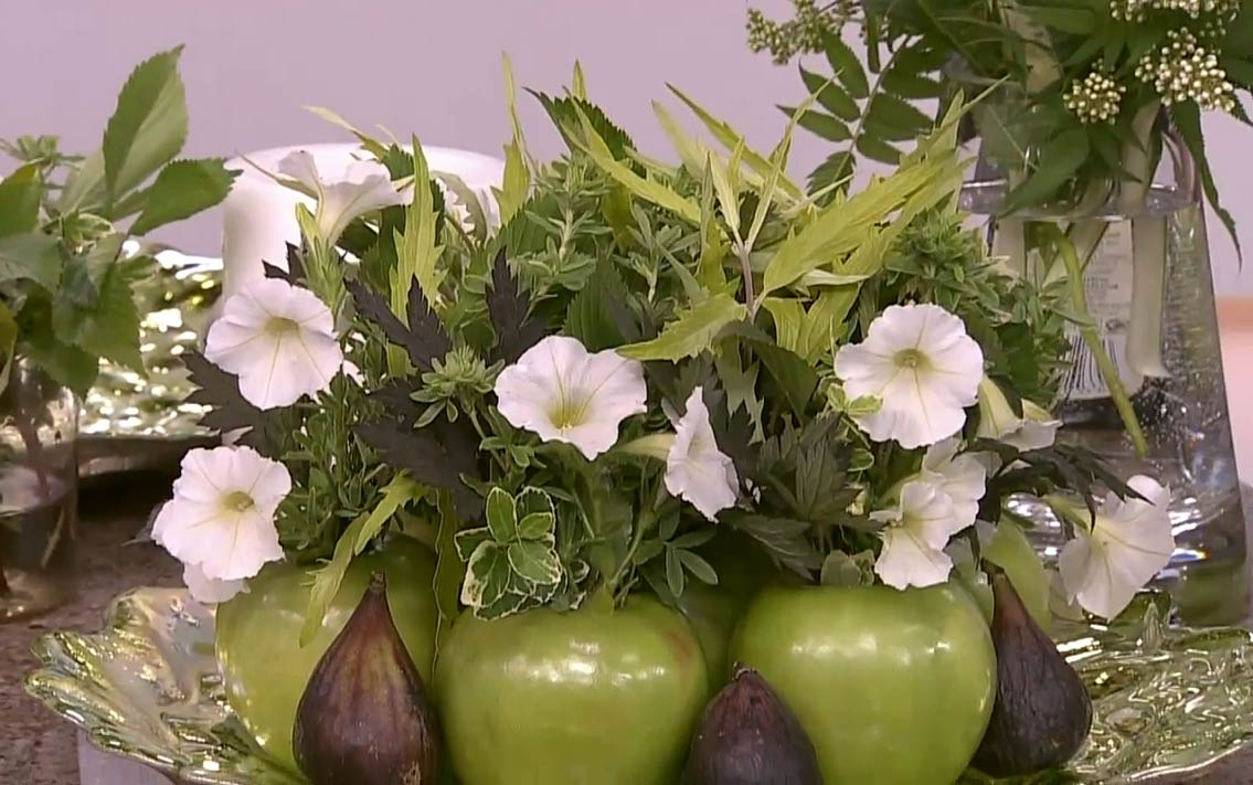 A close up shot of a table centerpiece made out of apple vases, figs, and garden florals.