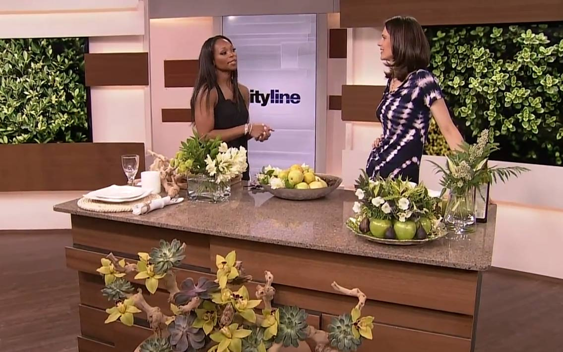 Celia Alida Rutte and Tracy Moore on the Cityline set with fruit and floral centerpieces on display.