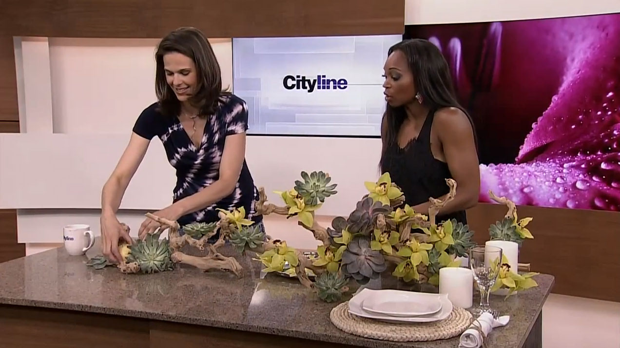 Celia places fruit and flowers into the arrangement, on the set of Cityline.