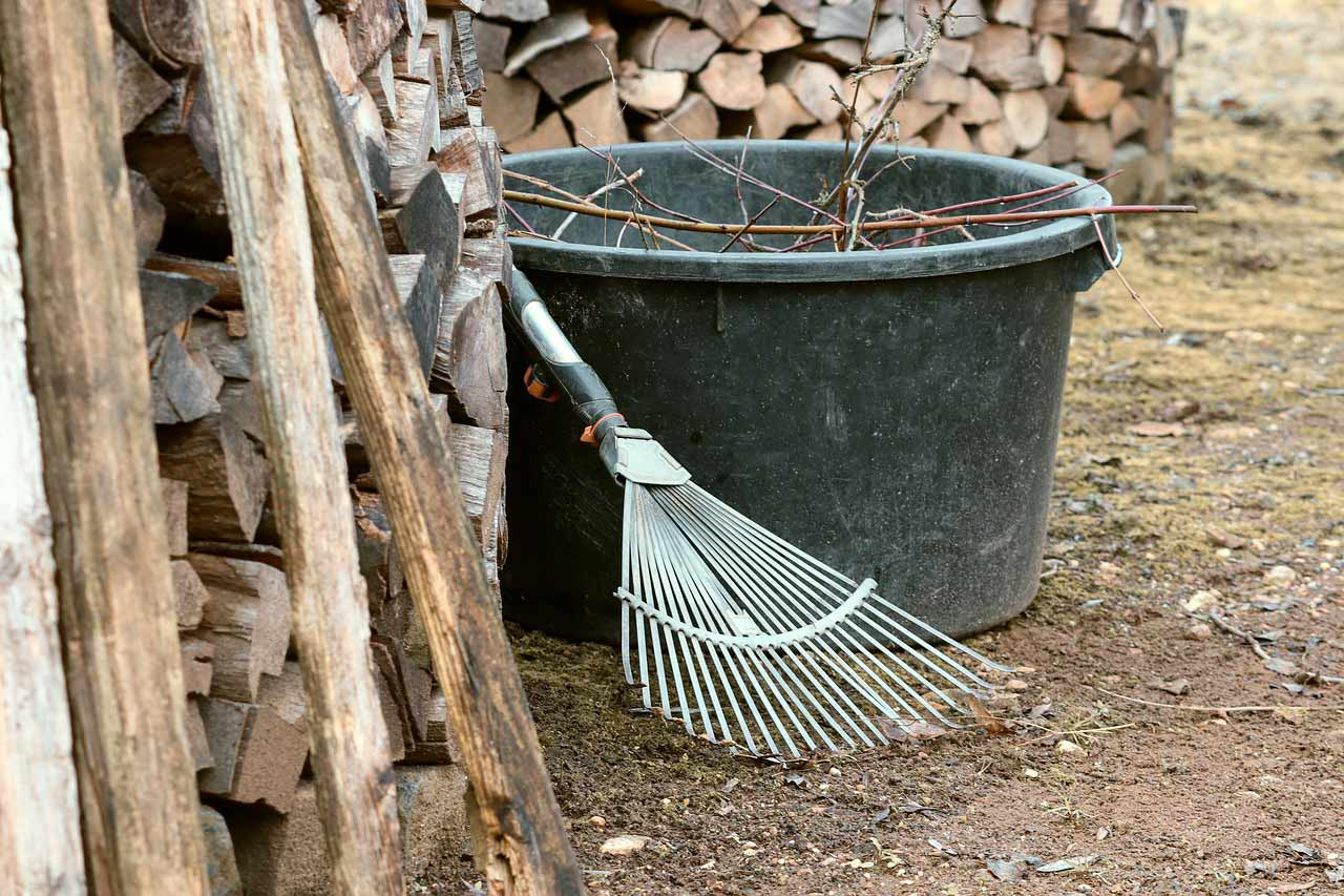 Piles of stacked firewood next to a bucket filled with twigs and a garden rake.